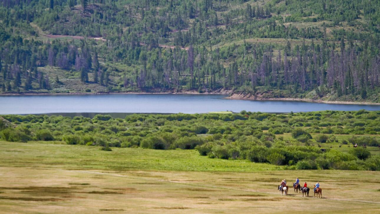 Group of people riding horses toward a lake