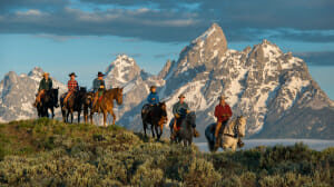 Group of people on horses with mountains in the background