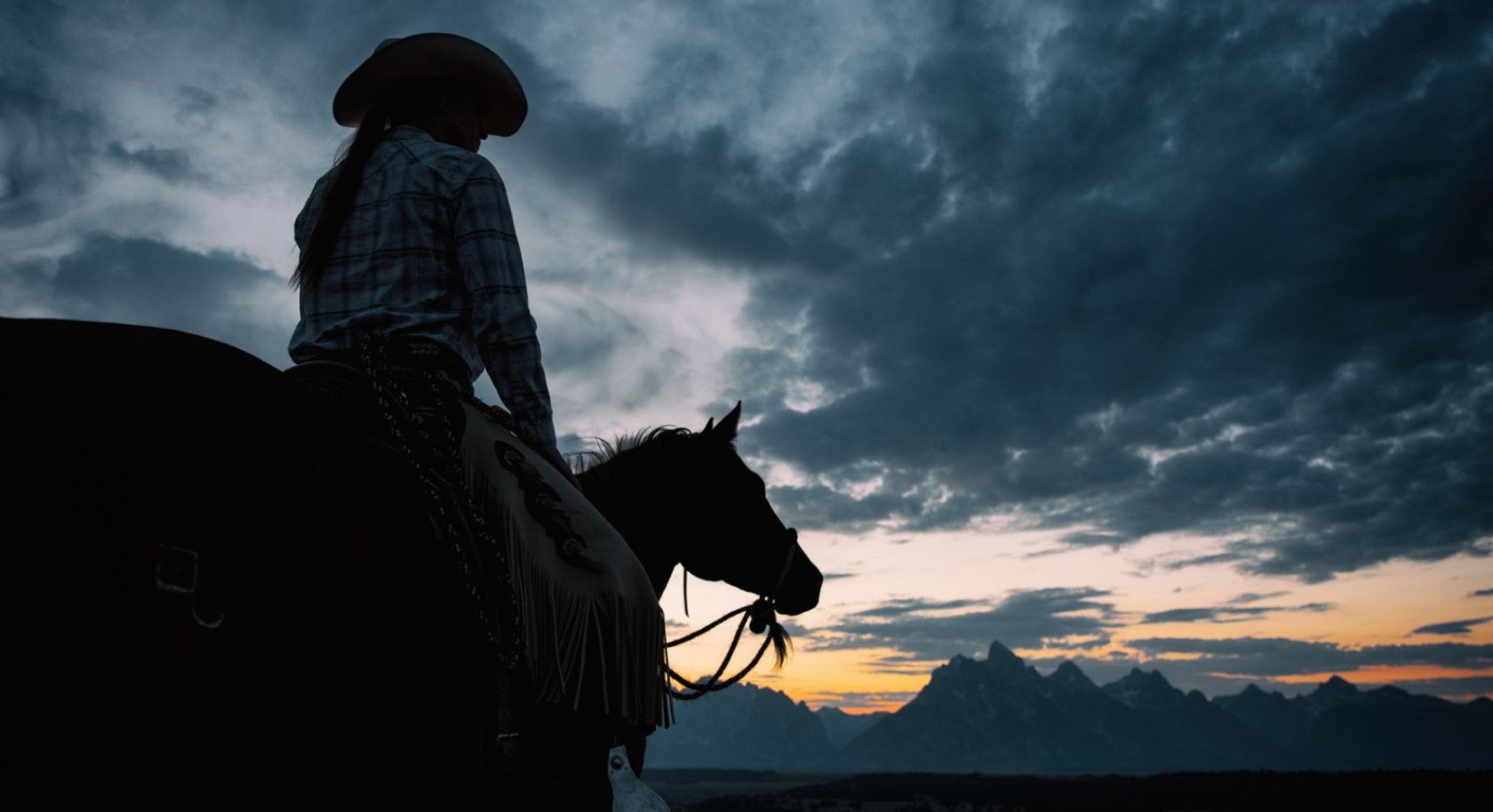 Woman on a horse looking out at the mountains at sunset