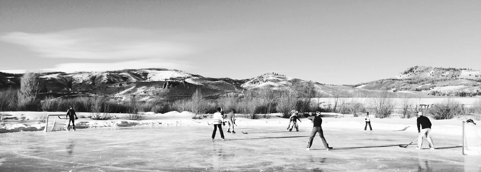 Old photo of people playing hockey on a frozen pond