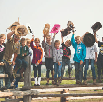 Group of kids sitting on a fence all holding their cowboy hats in the air