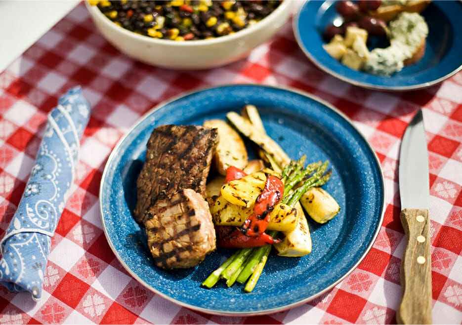 Plate of meat and vegetables on a picnic table