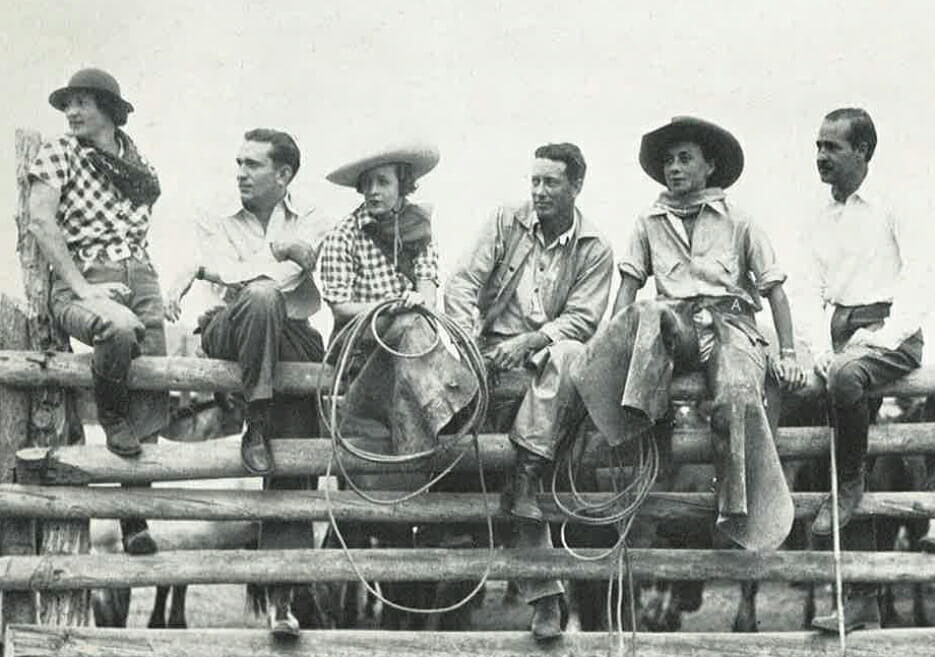 Old photo of a group of people sitting on a fence wearing riding clothes and holding lassoes