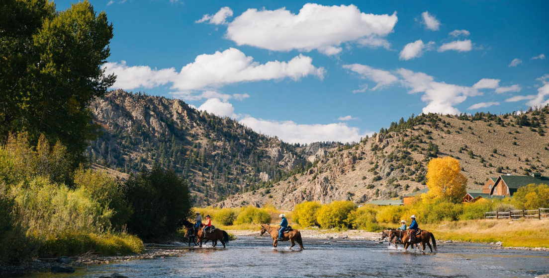Group of people riding horses across a river
