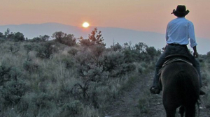 Man on a horse facing the sunset