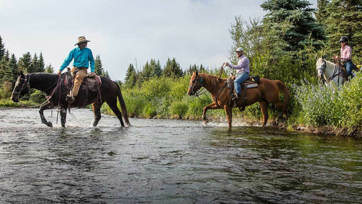 Horseback riding through a river at 4UR Ranch