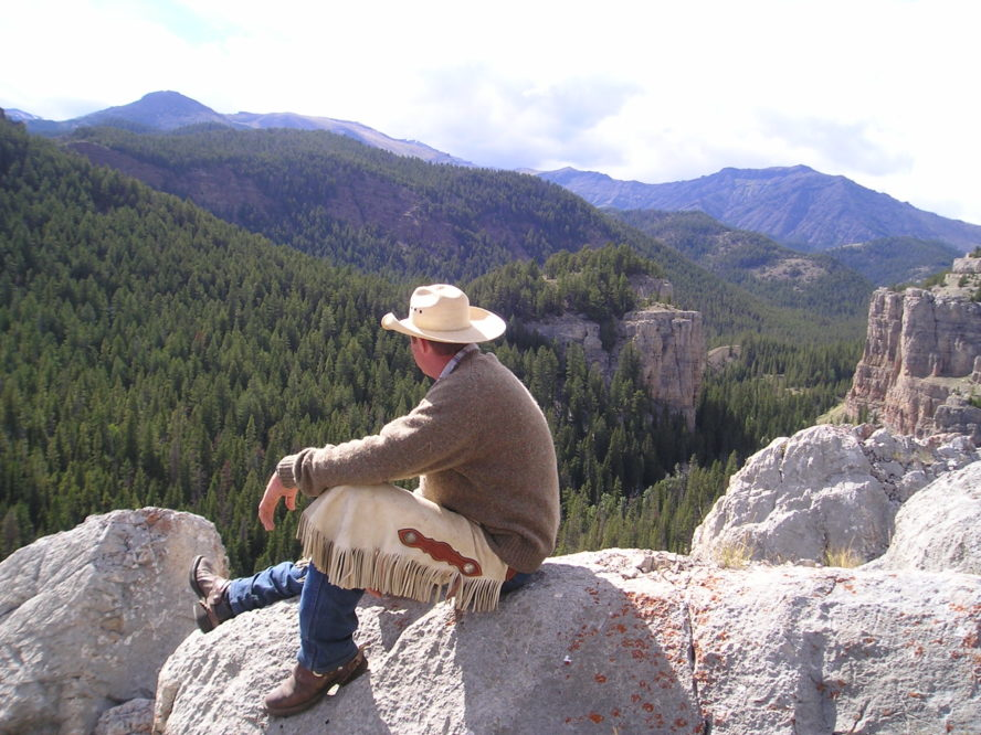 cowboy sitting on rocks overlooking a big mountain canyon