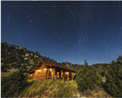 Cabin at dusk with stars in the dark blue sky