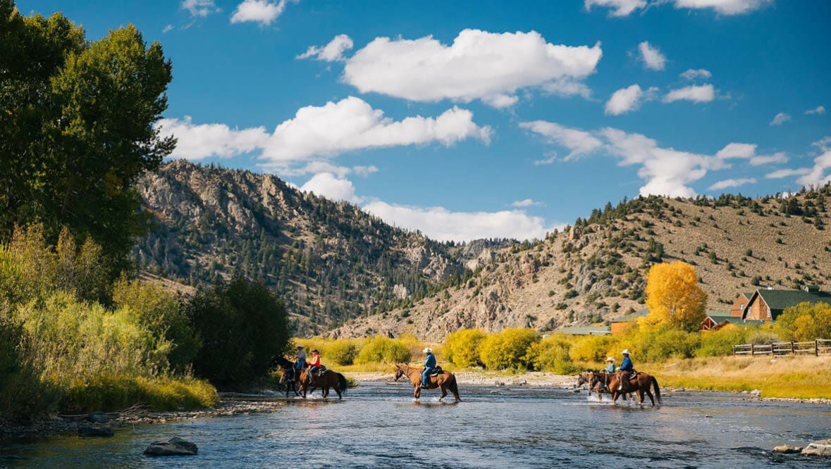 Riders crossing a river at A Bar A Ranch