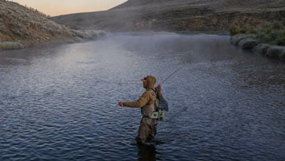 Guest fly fishing in a river with fog at A Bar A Ranch