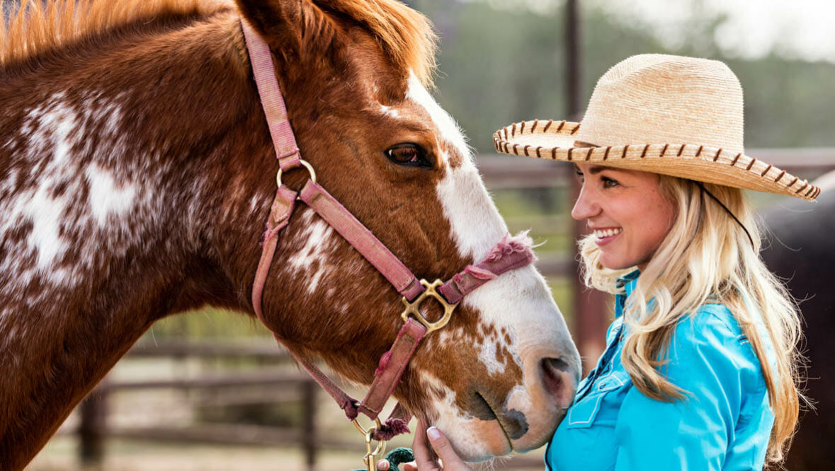 Cowgirl petting her horse at Alisal Guest Ranch
