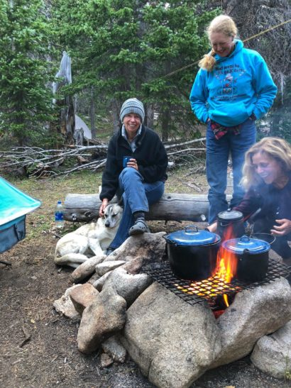 three women and dog around campfire cooking