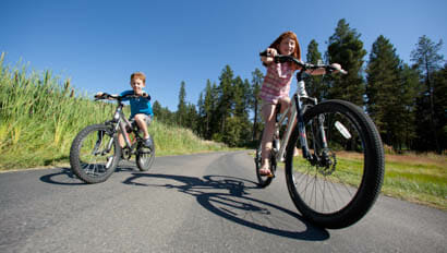 Two kids riding bikes at Averills Ranch