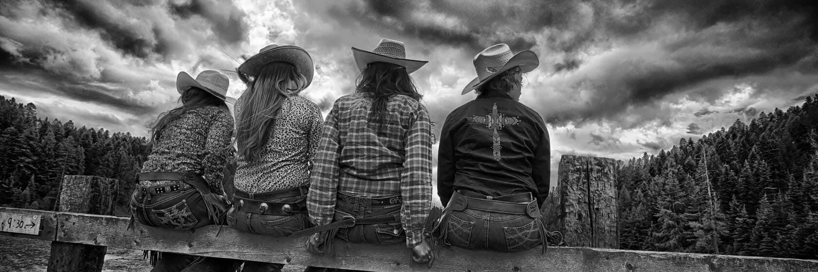 Four cowgirls sitting on a fence
