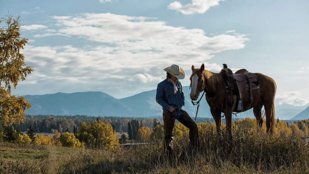 Cowboy standing next to his horse at Bar W Ranch