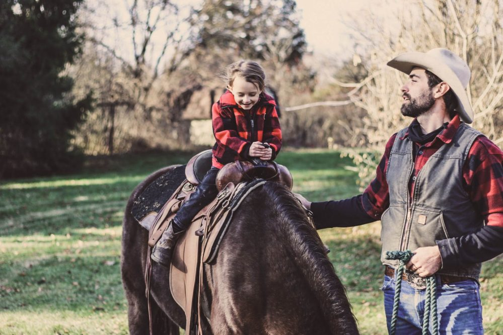 Little girl on a horse in red and black flannel with cowboy dad