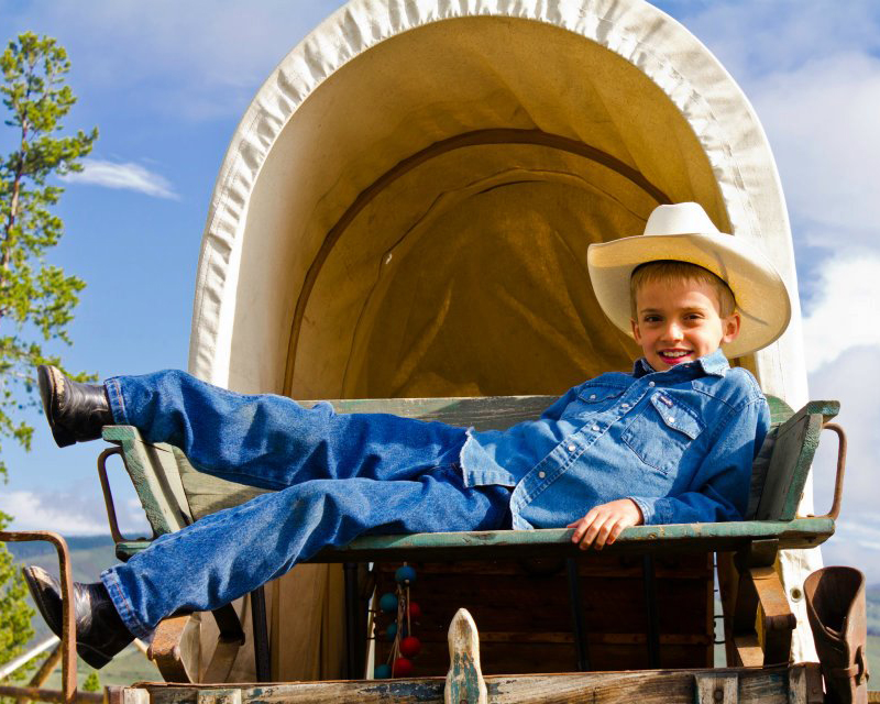 Kid in cowboy hat relaxing on a covered wagon