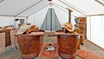 A couple in copper bath tubs in a tent at C Lazy U Ranch