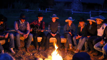Guests playing music around a camp fire at CM Ranch