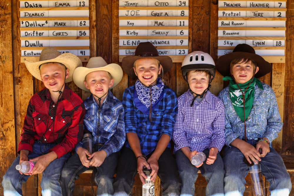 5 kids sitting on barn porch with cowboy hats and helmets