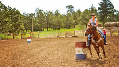 Woman riding in the barrel arena at Cherokee Park Ranch
