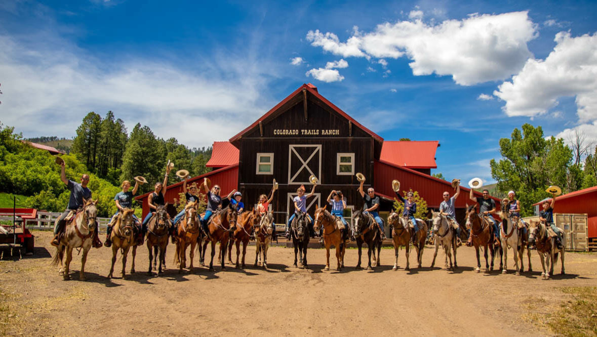 Family group on horses outside of a barn at Colorado Trails Ranch