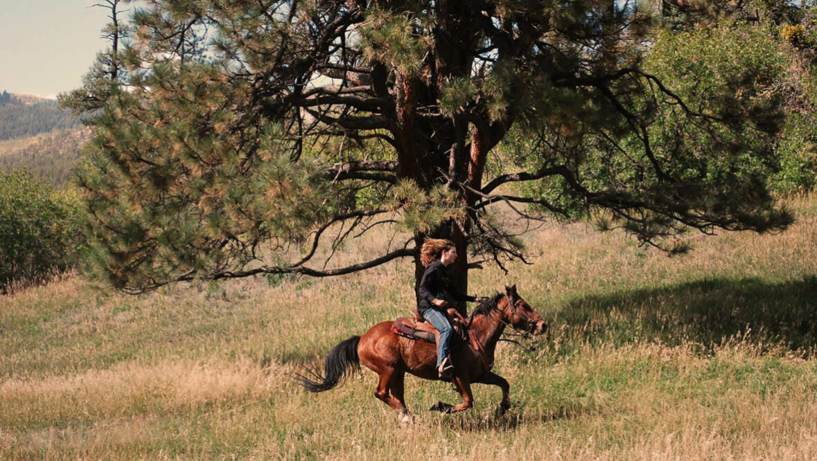 Cowgirl loping at Colorado Trails Ranch