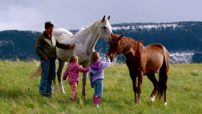 Kids petting retired horses at Covered Wagon Ranch