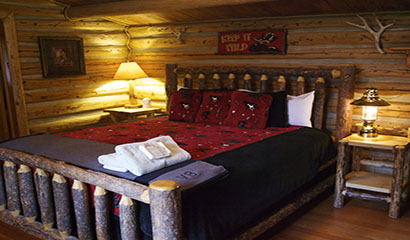 Covered Wagon Ranch Cabin with Red and Black Bed Spread and Towels
