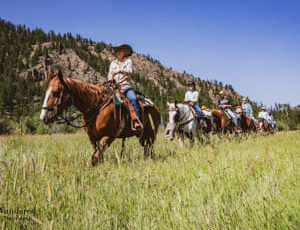 Trail ride through green field at Crossed Sabres Ranch