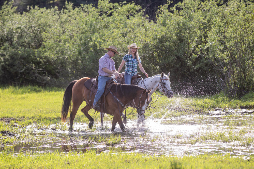 Western Pleasure Guest Ranch two riders in water riding green