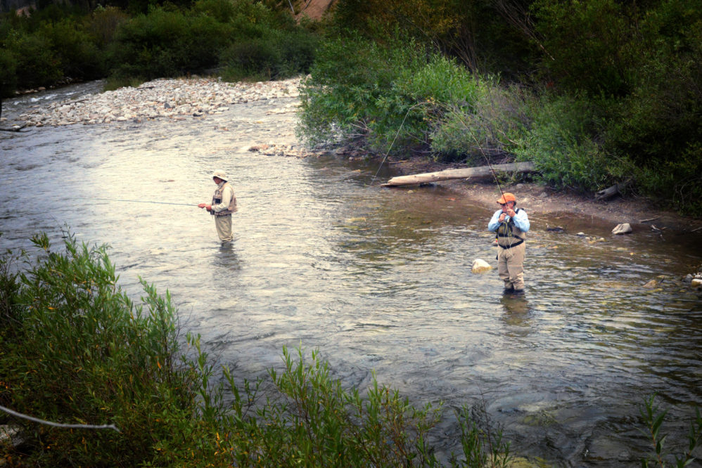 two people fly fishing in a river