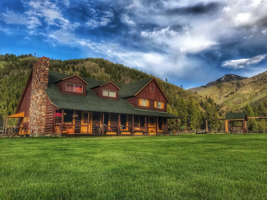 log cabin lodge with green lawn and blue sky with clouds