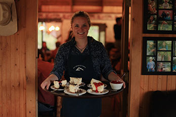 Elk Mountain Ranch young lady carrying tray of cheesecake