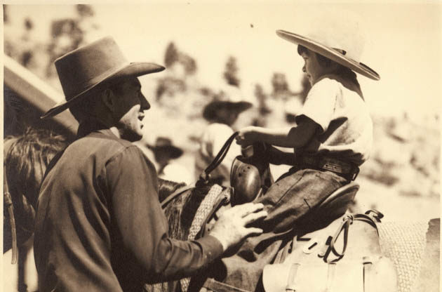 Historical photo of a father with his hand on his young son on a horse