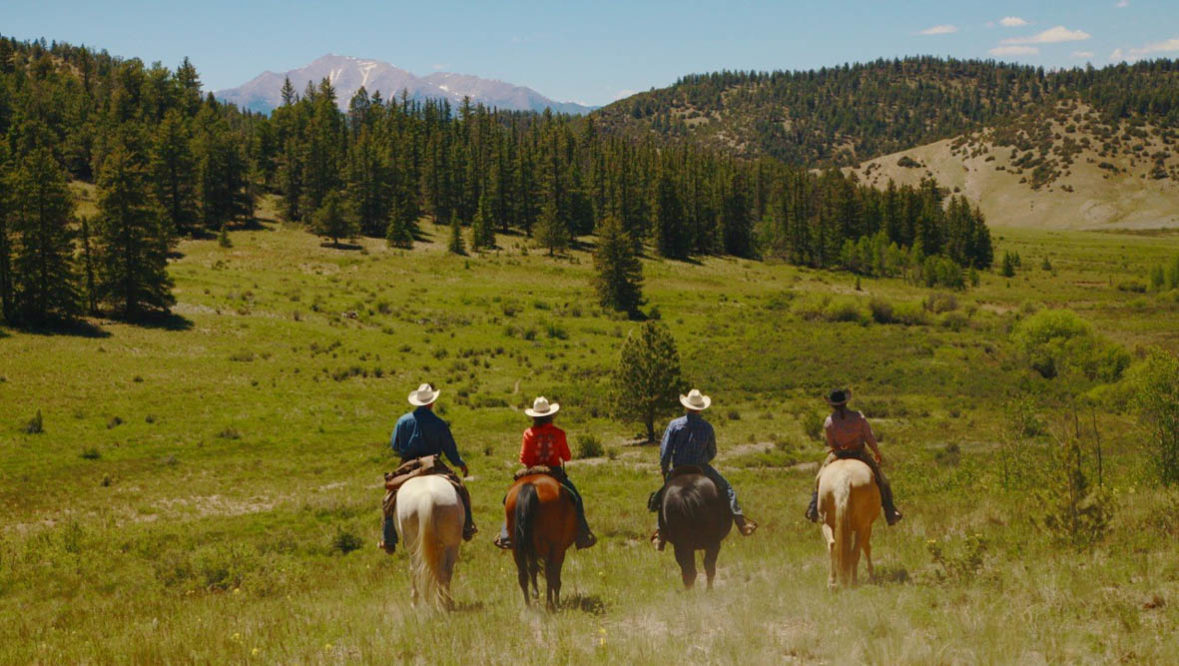 Four guests on horses at Elk Mountain Ranch