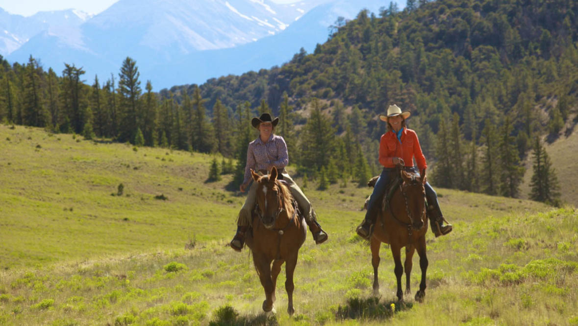 Two guests on horses at Elk Mountain Ranch