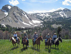 Guests on horses in a line in front of mountains at Elkhorn Ranch Montana