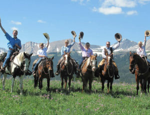 A family on horses raising their hats at Covered Wagon Ranch