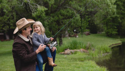 Dad holding young daughter as they fish together at Greenhorn Ranch