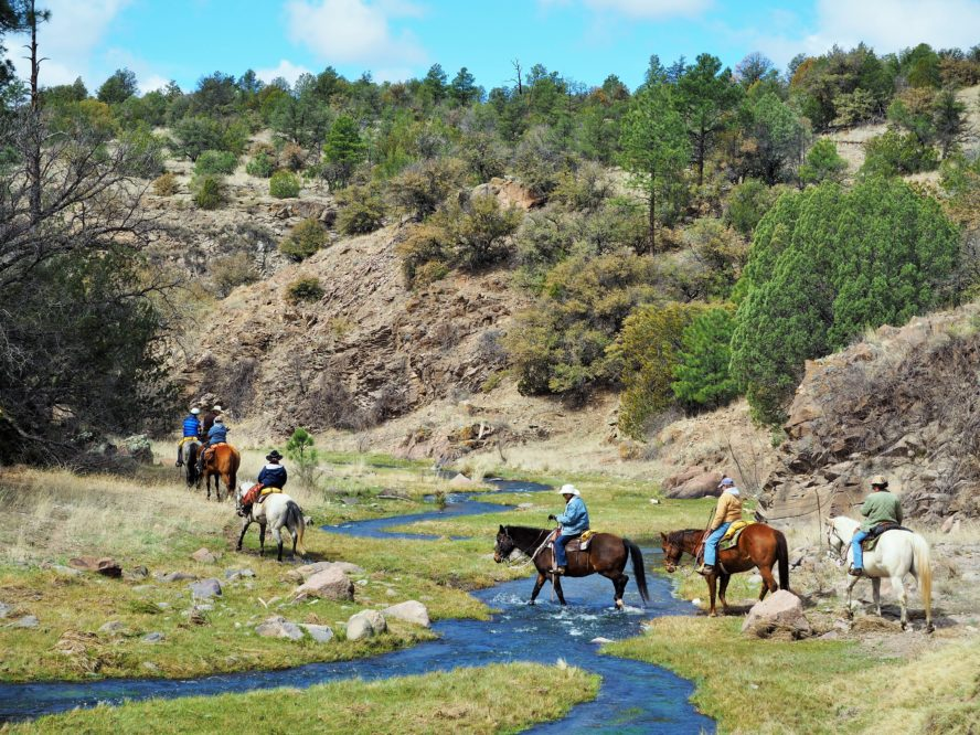 group of riders crossing stream in canyon