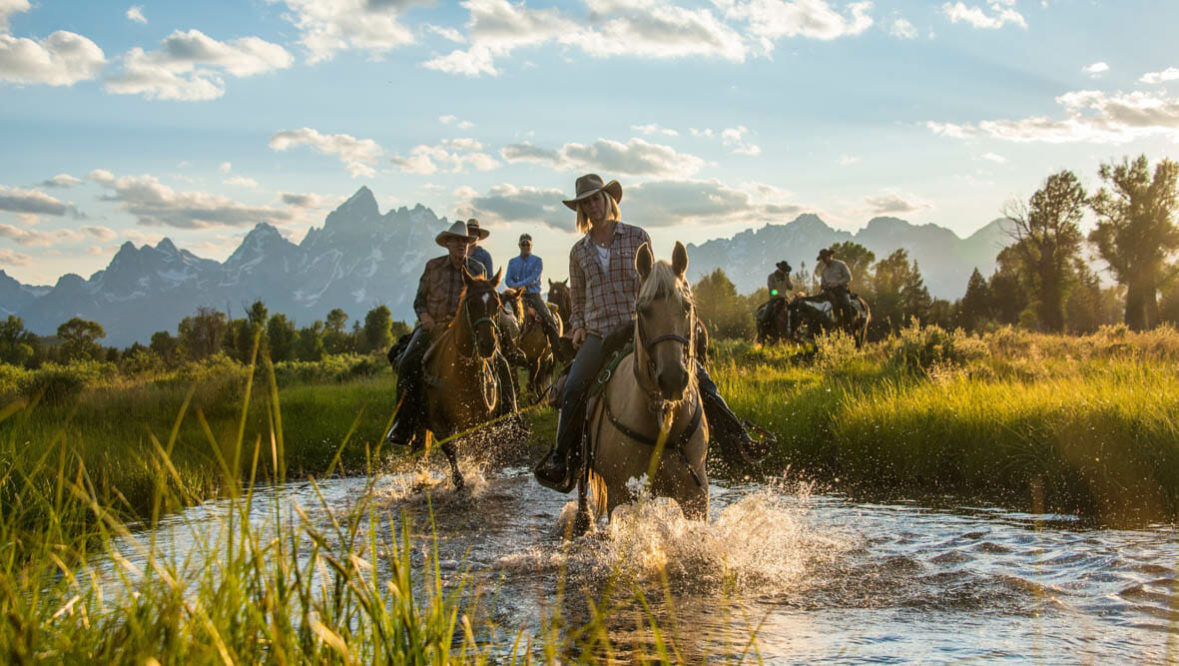 Riders and Horses crossing a river at Triangle X Ranch