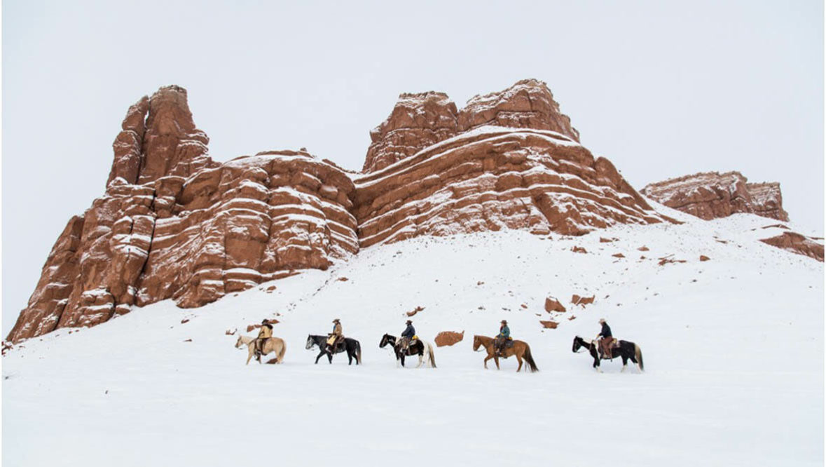 Trail ride in the snow by red rocks at Hideout Lodge Ranch