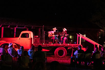 Hunewill Guest Ranch musical performance at night on back of old truck