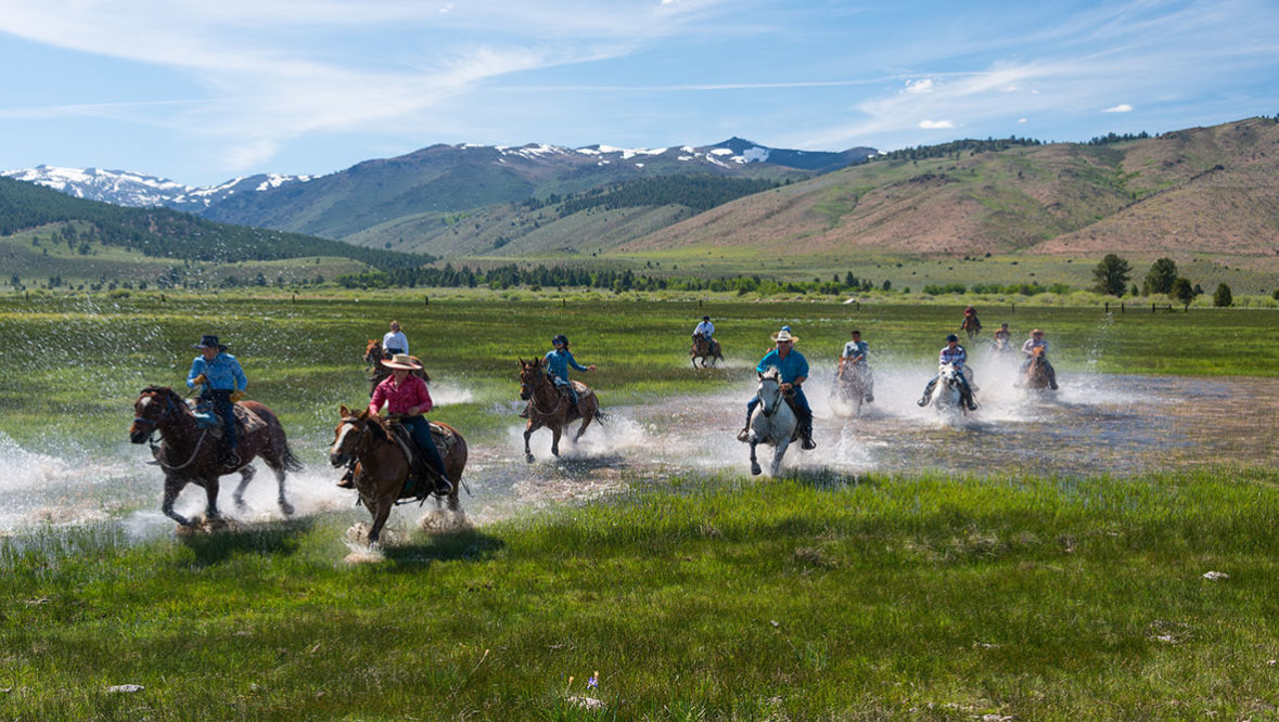 Hunewill Ranch riders splashing through water on horses