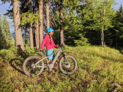 Lady with ebike in the mountains with green trees