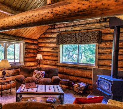 log cabin with woodstove and sitting furniture