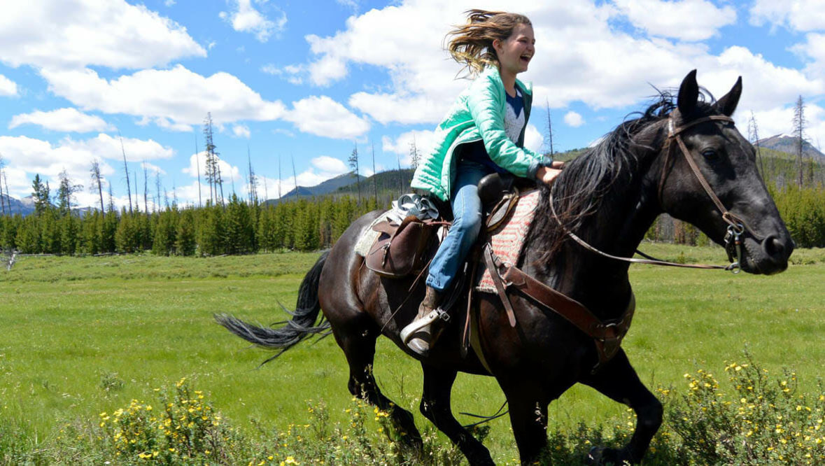 Girl loping on a horse at JJJ Wilderness Ranch