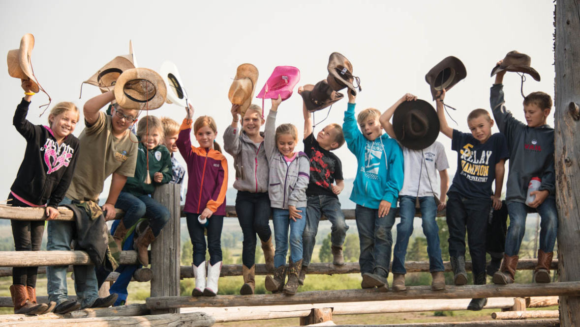 Kids in a line waving their cowboy hats in the air at Triangle X Ranch