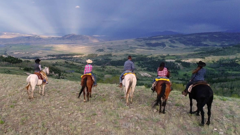 Line of horses and riders looking at the view at Latigo Dude Ranch